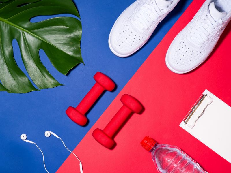Na kolorowym tle gadżety sportowe: hantle, buty do biegania, słuchawki, woda.