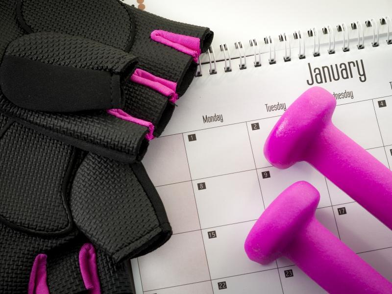 Na zdjęciu widok kalendarza na styczeń, obok leżą różowe hantle i rękawiczki sportowe.