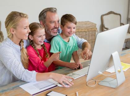 Rodzice z dziećmi przed komputerem.