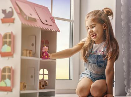 Dziewczynka bawi się domkiem dla lalek