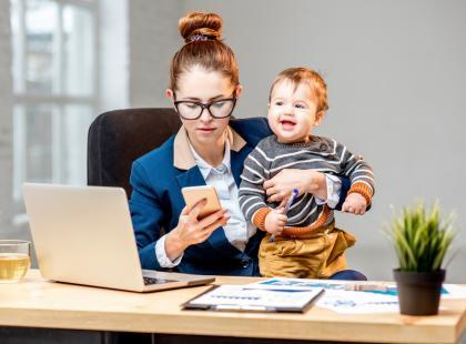 Kobieta z dzieckiem przed laptopem.