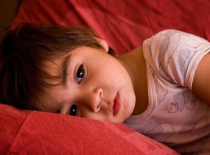 na kanapie leży smutne dziecko, któremu coś dokucza