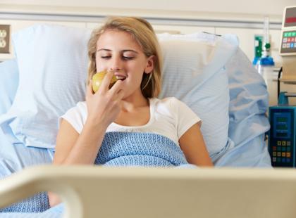 kobieta w szpitalnym łóżku je jabłko
