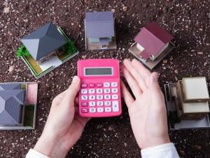 osoba z kalkulatorem obliczająca wartość domu