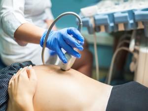 Brzuch kobiety ciężarnej w czasie badania USG.