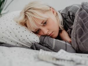 Smutna kobieta leżąca w łóżku