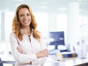Kobieta w białej koszuli stoi na tle biura.