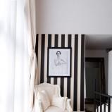 Wyjątkowe zestawienie czarno-białej tapety z bialym fotelem - propozycje od Homebook