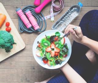 Widok na podłogę. Na podłodze po turecku siedzi kobieta, trzyma talerz z sałatką w ręku. Obok hantle, woda, warzywa, miarka krawiecka.