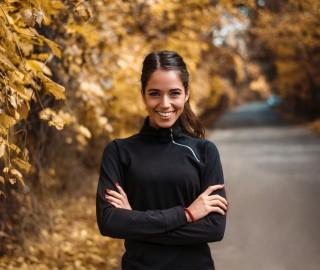 Wysportowana, młoda kobieta w czarnej bluzie na treningu w jesiennym parku.