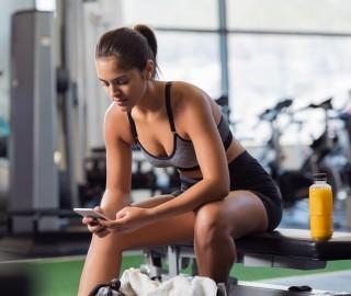 Młoda, zgrabna kobieta w stroju sportowym na siłowni. Kobieta siedzi i trzyma w ręku smartphone.