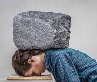 Kobieta przygnieciona kamieniem do biurka. Głowa kobiety leży na książce.