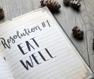 W notesie zapisane postanowienie noworoczne: jedz zdrowo! Notes na drewnianym blacie, wokół szyszki.