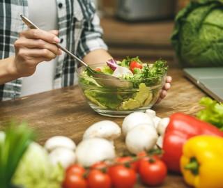 Zbliżenie na drewniany blat. Widać warzywa i dłonie kobiety, która przygotowuje sałatkę w przezroczystej miseczce.
