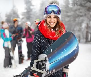 Młoda kobieta na stoku. Trzyma w ręku snowboard. W tle grupa przyjaciół.