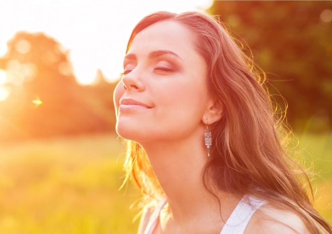 Młoda, ładna kobieta wystawia twarz w kierunku słońca.