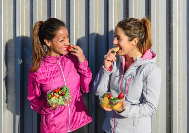 Dwie przyjaciółki w sportowych kurtkach jedzą sałatki z plastikowych pojemników.