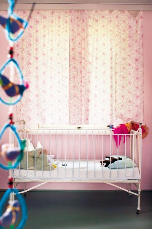 Small-cute-baby-bedroom-with-pink-walls-modern-small-bed-with-bedding-and-pillow-curtains-and-toys