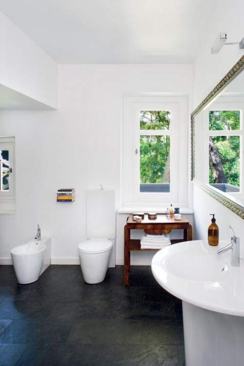 Luxury-white-and-bright-bathroom-design-with-toilet-bowl-modern-bidet-small-table-and-washbasin-with-mirror-and-sink
