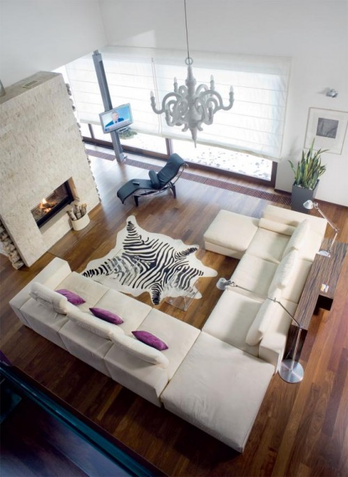 Luxury-large-living-room-design-with-modern-huge-sectional-sofa-with-ottoman-modern-leather-carpet-and-fireplace