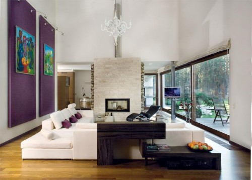Luxury-living-room-with-amazing-sofa-purple-wall-decoration-large-windows-fireplace-and-cupboards