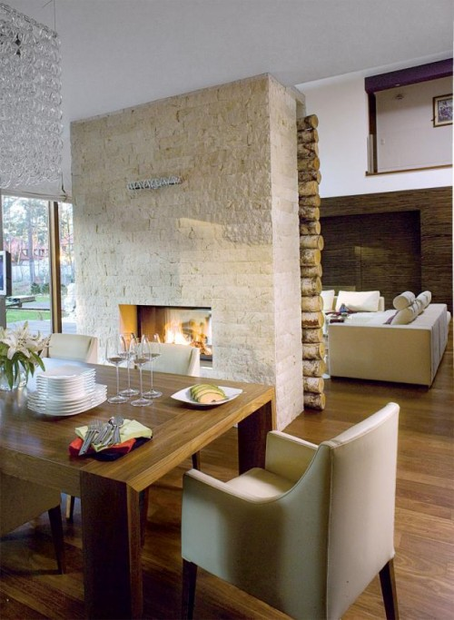 Luxury-dining-room-design-with-modern-wooden-dining-table-modern-leather-armchairs-indoor-fireplace-and-wall-decoration