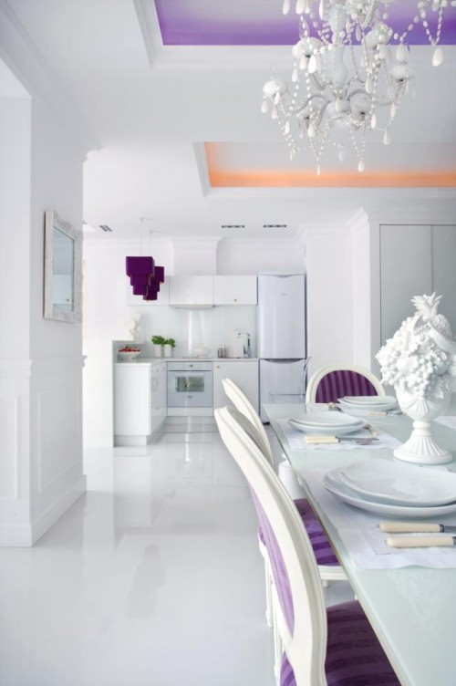Luxury-dining-room-area-with-white-purple-decorated-chairs-white-dining-table-and-view-to-minimalist-kitchen