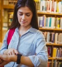 kobieta ze smartwatchem w bibliotece