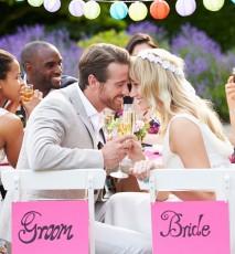 Para młoda przy stole z gośćmi weselnymi