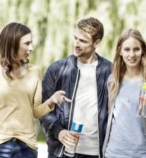 trzy osoby idą z butelkami Brita