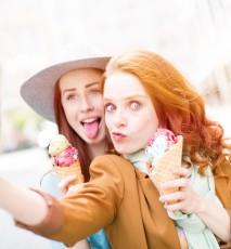 Kobiety jedzące lody w wafelku robiące sobie selfie