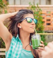Kobieta w okularach przeciwsłonecznych pijąca zielony koktajl.