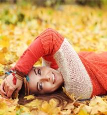 Młoda kobieta leży na jesiennych liściach