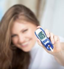Młoda kobieta trzymająca glukometr. Zbliżenie na glukometr.