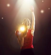 Kobieta uprawiająca boks, z uniesionymi dłońmi w geście zwycięstwa.