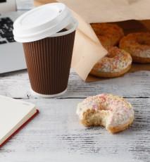 Na biurku leżą nadgryziony pączek, kawa, notes z długopisem i klawiatura.