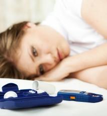 Smutna, młoda kobieta leży na łóżku. Obok widoczny glukometr dla cukrzyków.