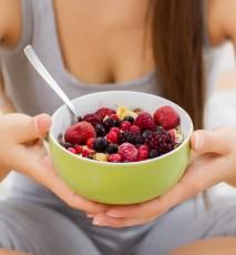 Widok na kobiece dłonie, które trzymają miseczkę z owsianką i dużą ilością owoców jagodowych.