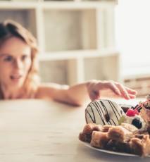 Młoda kobieta wybiera pomiędzy słodyczami a warzywami. Kieruje rękę w stronę słodyczy.