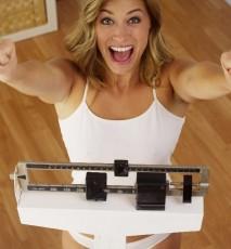 Szczęśliwa uśmiechnięta kobieta na wadze