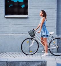 Młoda kobieta w niebieskiej sukience jedzie na rowerze.