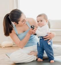 Młoda mama z małym dzieckiem siedzi na macie do ćwiczeń.