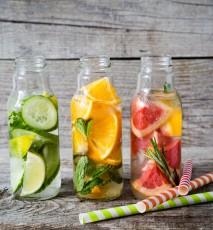 Wody smakowe z dodatkiem owoców i ziół w szklanych butelkach. Wody na tle drewnianego tła.