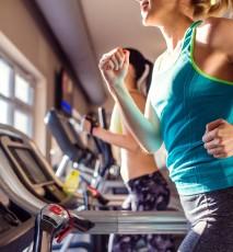 Zbliżenie na tułów kobiety, która biegnie na bieżni na siłowni.