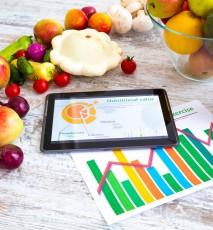 Na białym stole leżą warzywa i owoce. Obok tablet prezentujący na wykresie kołowym wartość odżywczą. Pod tabletem kartki z wykresami.