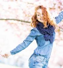 Radosna młoda kobieta w parku. W dłoni trzyma świeże kwiaty.