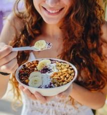 Kobieta trzyma w dłoniach miseczkę ze śniadaniem z owocami.