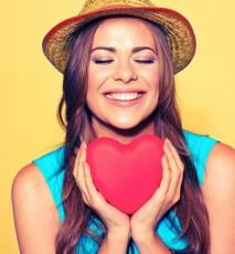 Młoda kobieta w kapeluszu trzyma w dłoniach drewniane serce.