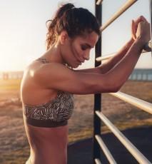 Młoda kobieta ćwiczy na zewnętrznej siłowni.