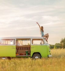 Młoda kobieta na wakacjach siedzi na dachu samochodu typu Kamper